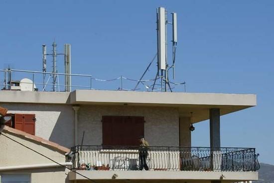 Un homme marche sur le balcon de son appartement, le 12 avril 2003 dans le quartier Saint-Jérôme, à Marseille, au-dessus duquel est installée une antenne-relais de téléphonie mobile.