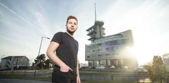 Le Glandois Marvin Grimm, âgé de 21 ans, est l'auteur d'une pétition pour un moratoire sur la 5G. Le voici au pied du bâtiment Odyssea de l'EPFL, sur le toit duquel se trouve l'une des premières antennes 5G de Swisscom. (Photo: Sébastien Anex)