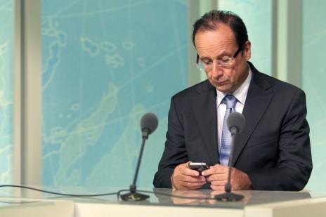 François Hollande regarde son smartphone dans les studios de Martinique première, le 4 juillet 2011 (Patrick Coppée/AFP)