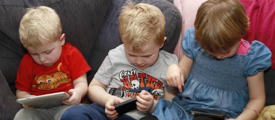 Des enfants de 3, 6 et 5 ans utilisant smartphones et tablettes (illustration). © ANGOT/SIPA